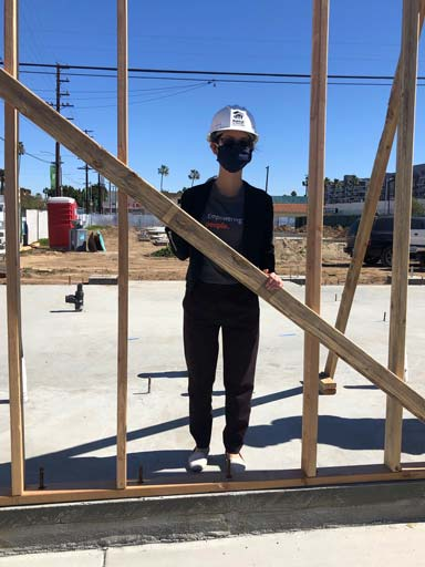 Sarah with hard hat and mask signing a beam for one of the walls
